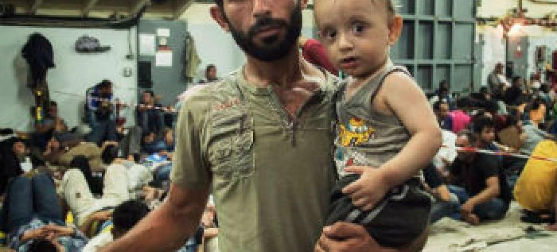 Homem sírio com seu filho de um ano de idade que foram resgatados no Mediterrâneo. Foto: Acnur/A. D'Amato