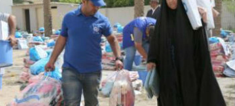 Funcionários da OIM distribuem itens de ajuda para iraquianos deslocados. Foto: OIM