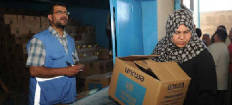 Funcionário da agência entrega alimentos a mulher refugiada. Foto: Unrwa/Shareef Sarhan
