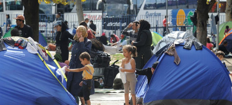 Crianças, mulheres e homens que fugiram de suas casas em meio à crise de refugiados e migrantes em curso ao lado de tendas em Belgrado, capital da Sérvia. Foto: Unicef/ Shubuckl