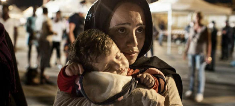 Mulher síria com filho nos braços à chegada do porto de Palermo, em Itália. Foto: Acnur/Alessandro Penso