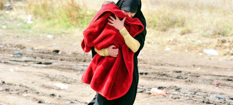 Mulher carregando criança na cidade de Presevo, Sérvia, na fronteira com a Macedônia. Foto: Unicef/Tomislav Georgiev