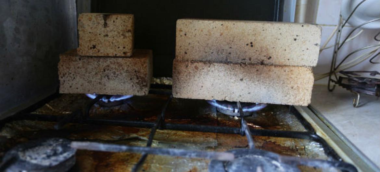 Famílias que estão vivendo em áreas afetadas pelo conflito no leste da Ucrânia tentam manter suas casas aquecidas colocando tijolos no fogão a gás. Foto: Unicef/ Alexey Filippov