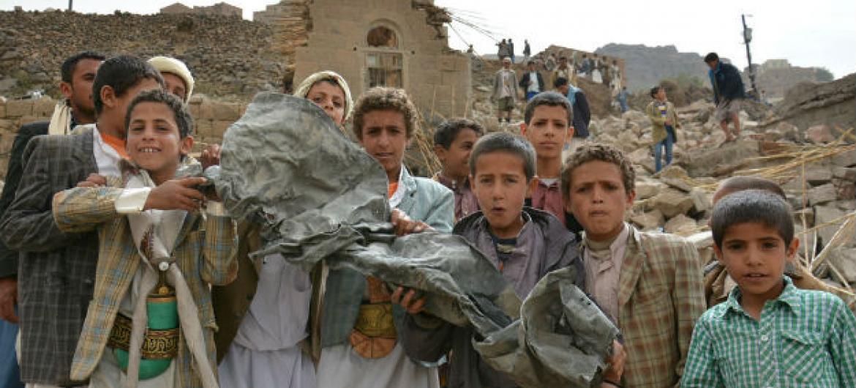 Crianças seguram um pedaço de metal no meio de casas destruídas por bombardeamentos aéreos. Foto: Unicef/Mohammed Hamoud