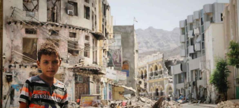Criança iemenita ao lado de prédios destruídos devido aos confrontos no país. Foto: Unicef
