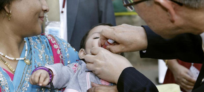 Secretário-geral, Ban Ki-moon, administra dose de vacina da pólio a uma criança levada pela mãe ao complexo da ONU em Nova Déli, Índia, em outubro de 2008. Foto: ONU/Mark Garten