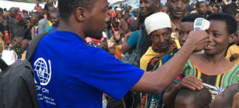 Funcionario da OIM com pessoas em busca de abrigo. Foto: OIM (arquivo)