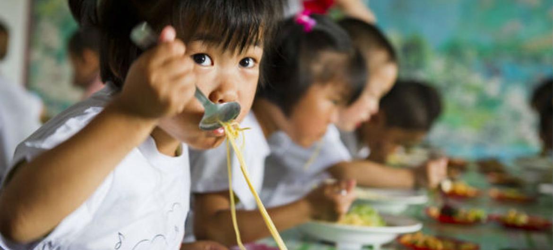 Crianças na Coreia do Norte comem comida fornecida pelo PMA. Foto: PMA/Rein Skullerud (arquivo)