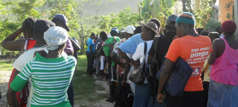 Homens e mulheres formam fila para receber sementes em Jeremie, na área de Grand'Anse. Foto: FAO/Justine Texier