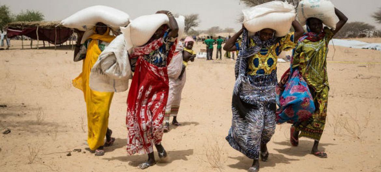 Pessoas que vivem no campo para deslocados internos de Melia, no Lago Chade, recebendo comida do Programa Mundial de Alimentos, PMA. Foto: PMA/Marco Frattini