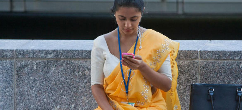 Jovem usa celular em Washington, nos Estados Unidos. Foto: Banco Mundial/Simone D. McCourtie