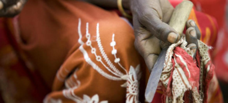 Em encontro comunitário na vila de Kabele, na Etiópia, ex-praticande de mutilação genital feminina segura a ferramenta utilizada por ela para realizar o procedimento. Foto: Unicef/UNI77840/Holt