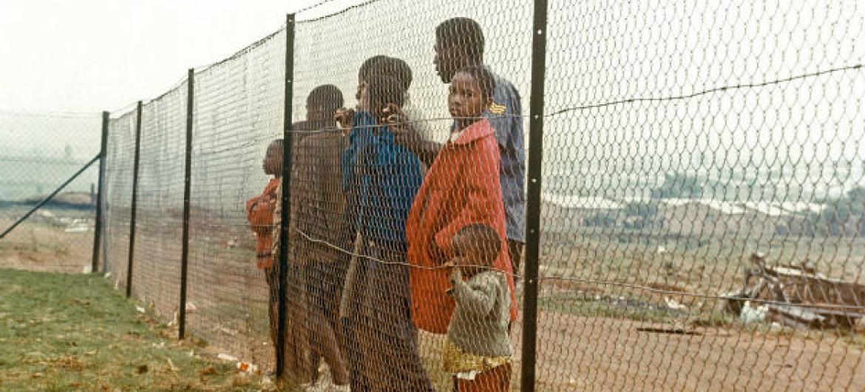 Crianças atrás da cerca que as separava da comunidade branca perto de Joanesburgo, na África do Sul, durante o apartheid. Foto: ONU/Pendl