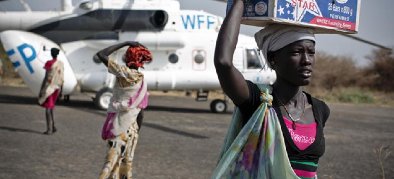 Mulher carrega kit de emergência alimentar entregue por um helicóptero do Programa Mundial de Alimentos no Sudão do Sul. Foto: Unicef/Holt