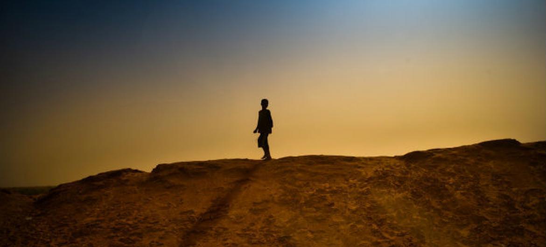 Menino caminha ao lado de um acampamento para refugiados na Mauritânia. Foto: Unicef/Dragaj