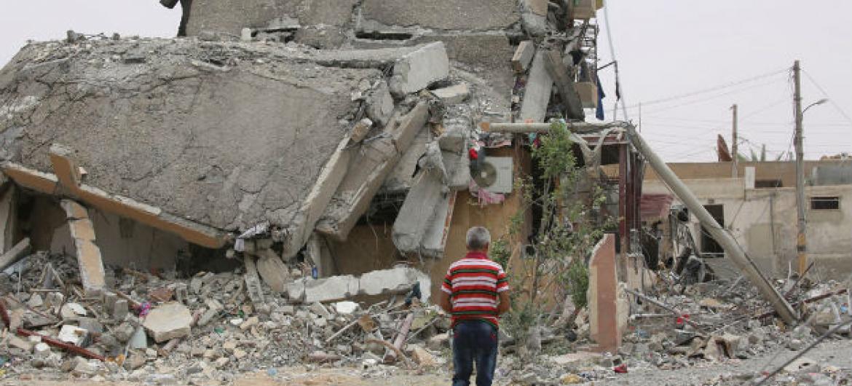 Uma pessa em meio a destroços de um prédio na cidade de Tabqa, província de Raqqa, na Síria. Foto: Unicef/Souleiman
