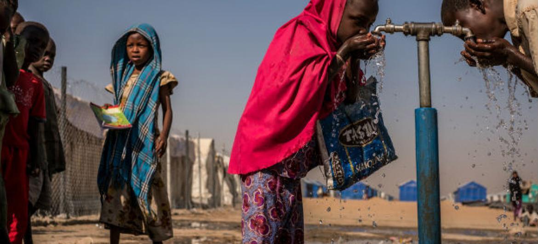Crianças bebem água em uma torneira durante o recesso em uma escola primária apoiada pelo Unicef dentro do campo para pessoas deslocadas internamente de Bukasi, em Maiduguri, estado de Borno, Nigéria. Foto: Unicef/ Gilbertson
