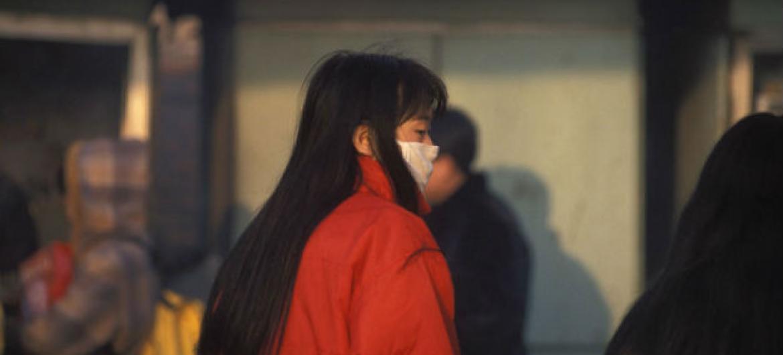 Mulher usa máscara para se proteger da poluição. Foto: Banco Mundial/ Curt Carnemark