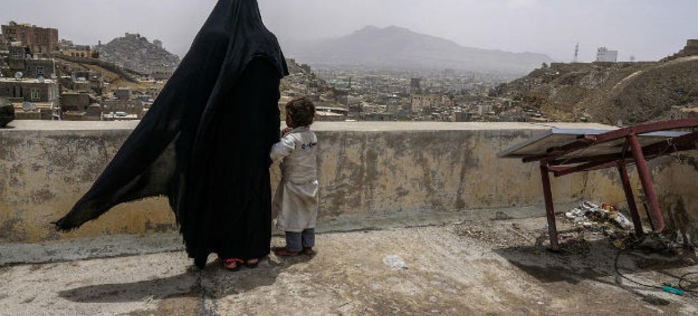 Uma mulher deslocada internamente e sua filha olham a cidade de Sanaa, no Iêmen, a partir do telhado do prédio onde está abrigada. Foto: Giles Clarke/ Ocha.