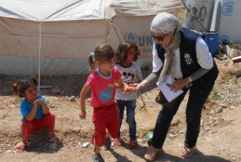 Crianças deslocadas com funcionária da OMS. Foto: OMS Iraque