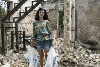 Mulher no meio de destroços na Ucrânia. Foto: Acnur/I.Zimova