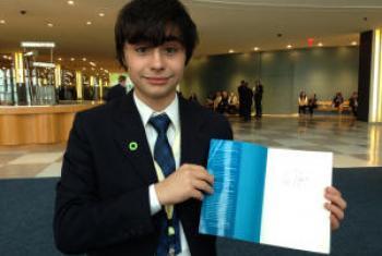João Pedro Eboli mostra o livro autografado por Al Gore. Foto: Rádio ONU