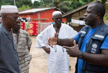 Funcionário da OMS ajuda comunidade na Serra Leoa. Foto: OMS/C. Black