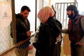 Homem sírio recebe doação de sapatos a seus filhos. Foto: OIM