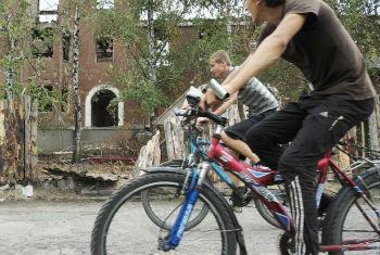 Ciclistas passam por um prédio residencial destruído, na região de Donetsk. Foto: Acnur/I.Zimova