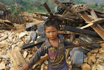 Criança nepalesa no meio de destroços. Foto: Unicef