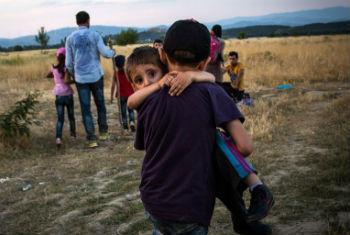Menino sírio carrega irmão ao cruzarem fronteira. Foto: Acnur/A. McConnel