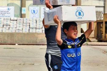 Menino iraquiano pega pacote com comida fornecido pelo PMA. Foto: PMA//Mohammed Al Bahbahani