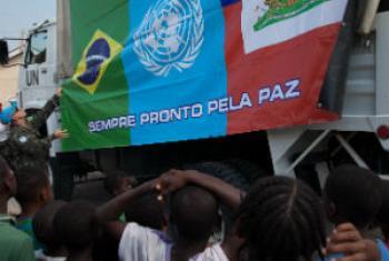 Crianças haitianas observam bandeiras. Foto: ONU/Nektarios Markogiannis