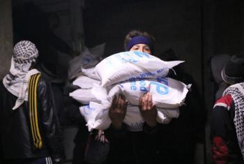 Em Madaya, membros da comunidade local ajudam a descarregar e distribuir itens de ajuda humanitária. Foto: PMA/Hussam Al Saleh