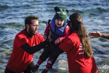 Voluntários ajudam criança a sair do barco em Lesbos, Grécia. Foto: Acnur/Achilleas Zavallis