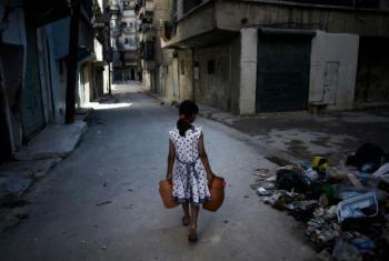 Menina carrega dois jarros de água numa rua em Aleppo. Foto: Unicef/Romenzi