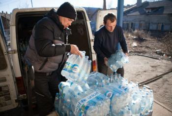 Em fevereiro de 2015, voluntários descarregam suprimento de garrafas d'água enviado pelo Unicef em Donetsk Oblast, na Ucrânia. Foto: Unicef/Aleksey Filippov