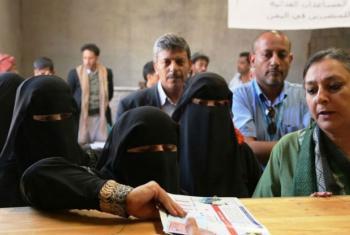 Mulher iemnita recebe cupões alimentares em centro de ajuda. Foto: PMA/Fares Khoailed