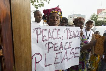Mulher carrega cartaz com mensagem de paz na República Democrática do Congo. Foto: ONU/Eskinder Debebe