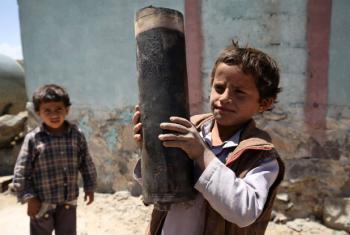 Menino segura um pedaço de um foguete que explodiu perto do vilarejo de Al Mahjar, subúrbio de Sanaa, a capital do Iêmen. Foto: UNICEF/Mohamed Hamoud