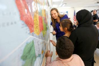 Jovens refugiados sírios estudam mapa dos Estados Unidos. Foto: Victoria Hazou/OIM