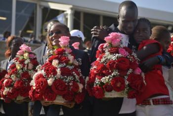 O atleta olímpico Yiech Pur Biel (à dir.) é abraçado por um parente em sua chegada à Nairóbi, no Quênia. Ele foi um dos cinco sul-sudaneses que fez história ao competir na primeira Equipe Olímpica de Atletas Refugiados nos Jogos Rio 2016. Foto: Acnur/Tony