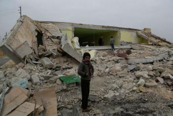 Criança em frente aos destroços de sua escola na vila Ainjara, zona rural de Alepo, na Síria. Foto: Unicef/Khalil Alshawi