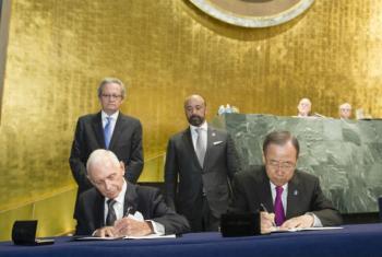 Ban Ki-moon (à dir.) e o chefe da OIM, William Lacy Swing, assinam o acordo entre ONU em OIM. Foto: ONU/Rick Bajornas