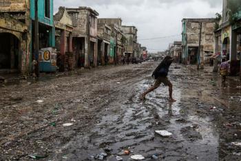 Mulher atravessa rua em Porto Príncipe após a passagem do furacão Matthew, em 4 de outubro de 2016. Foto: Minustah/Logan Abassi