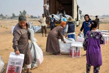 Deslocados internos em Qayyara, perto de Mosul, recebem itens de assistência da OIM. Foto: OIM