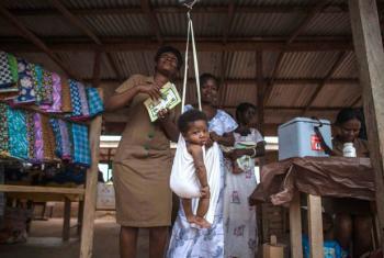 Em Gana, um trabalhor de saúde comunitária pesa bebês após vaciná-los. Em 2012, Gana se tornou o primeiro país na África a introduzir simultaneamente vacinas contra doenças pneumocócicas e rotavírus, tendo como peneumonia e diarreia, grandes causadores de