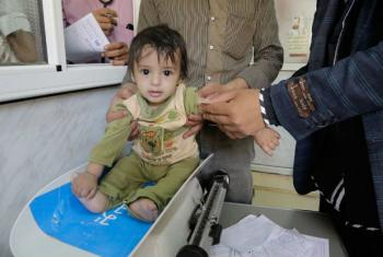 Criança iemnita sendo pesada em um centro de saúde. Foto: Unicef/Ma'ad Al-Zekri