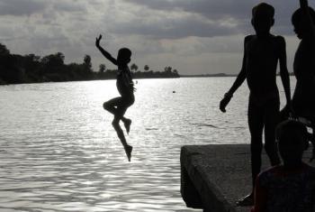 Criança pula em rio na Gâmbia. Foto: Ocha/Ivo Brandau (arquivo)