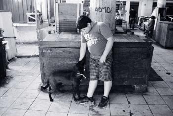 Criança acima do peso brinca com seu cachorro em um mercado em Assunção, no Paraguai. Foto: ONU News/ Rocío Franco